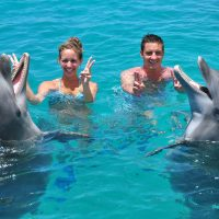 Two tourists enjoying their dolphin encounter at the Dolphin Academy Curaçao.